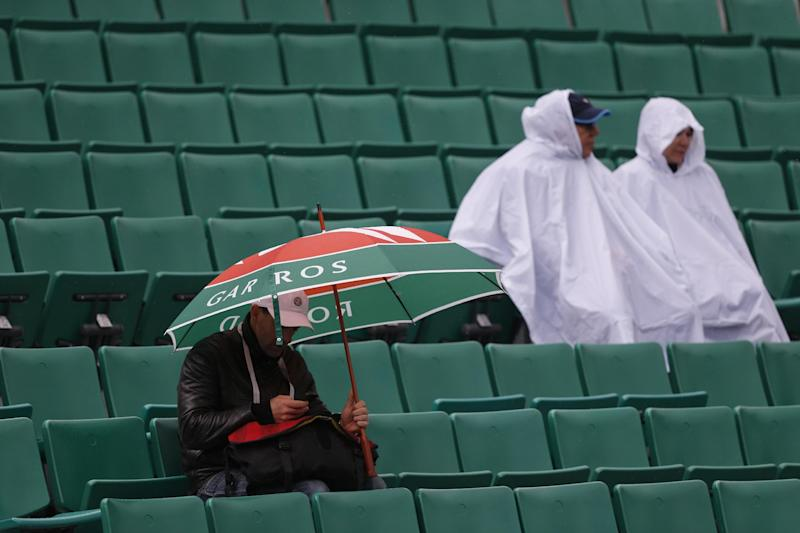 Spectators shield themselves as rain interrupts matches as the French Open tennis tournament, at Roland Garros stadium in Paris, Thursday, May 30, 2013. (AP Photo/Petr David Josek)