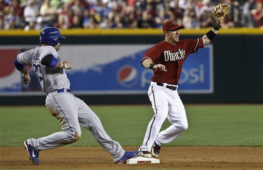Los Angeles Dodgers' Adrian Gonzalez, left, gets back to second base just in time to be the throw to Arizona Diamondbacks' Cliff Pennington during the seventh inning in a baseball game, on Sunday, April 14, 2013 in Phoenix. The Diamondbacks defeated the Dodgers 1-0. (AP Photo/Ross D. Franklin)