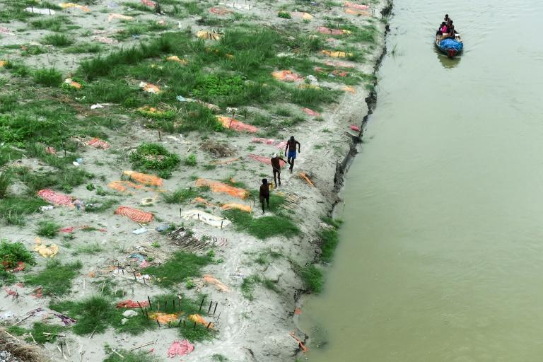 Seasonal flooding of India's Ganges river flushed out shallow graves where hundreds were buried at the peak of the crisis