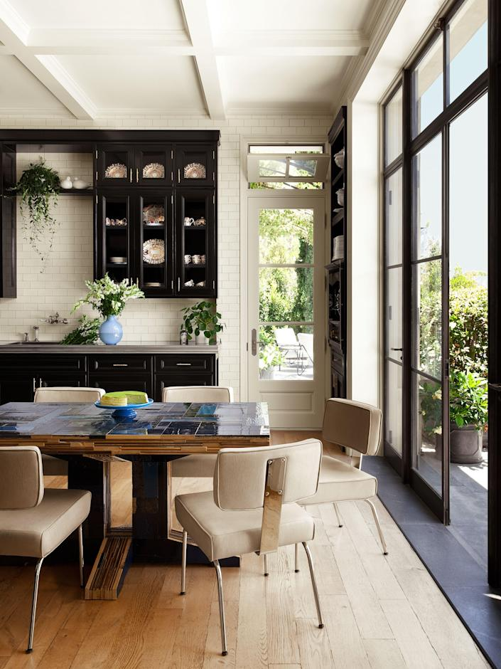 The kitchen has a Piet Hein Eek table, Richard Neutra chairs by VS America, and Waterworks fittings.
