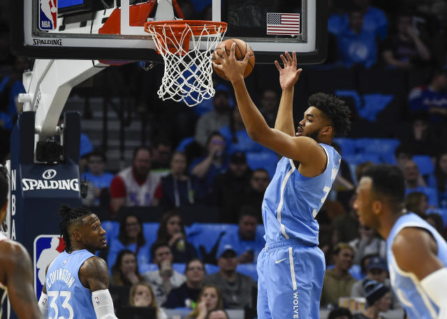 Minnesota Timberwolves center Karl-Anthony Towns, center,grabs a rebound against the Los Angeles Clippers as Timberwolves forward Robert Covington(33) looks on during the first half of an NBA basketball game Friday, Dec. 13, 2019, in Minneapolis. (AP Photo/Craig Lassig)