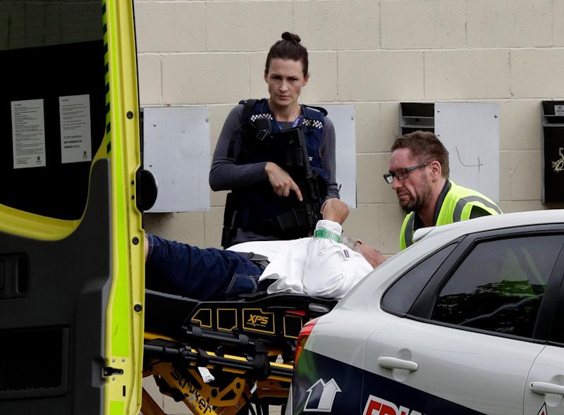 An armed police officer watches as a man is taken by ambulance staff from a mosque in central Christchurch, New Zealand, March 15, 2019. (Photo: Mark Baker/AP)