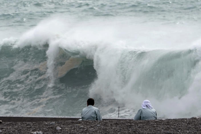 Men look at surging waves as Typhoon Hagibis approaches at a port in town of Kiho, Mie Prefecture, Japan Friday, Oct. 11, 2019. A powerful typhoon is advancing toward the Tokyo area, where torrential rains are expected this weekend. (AP Photo/Toru Hanai)