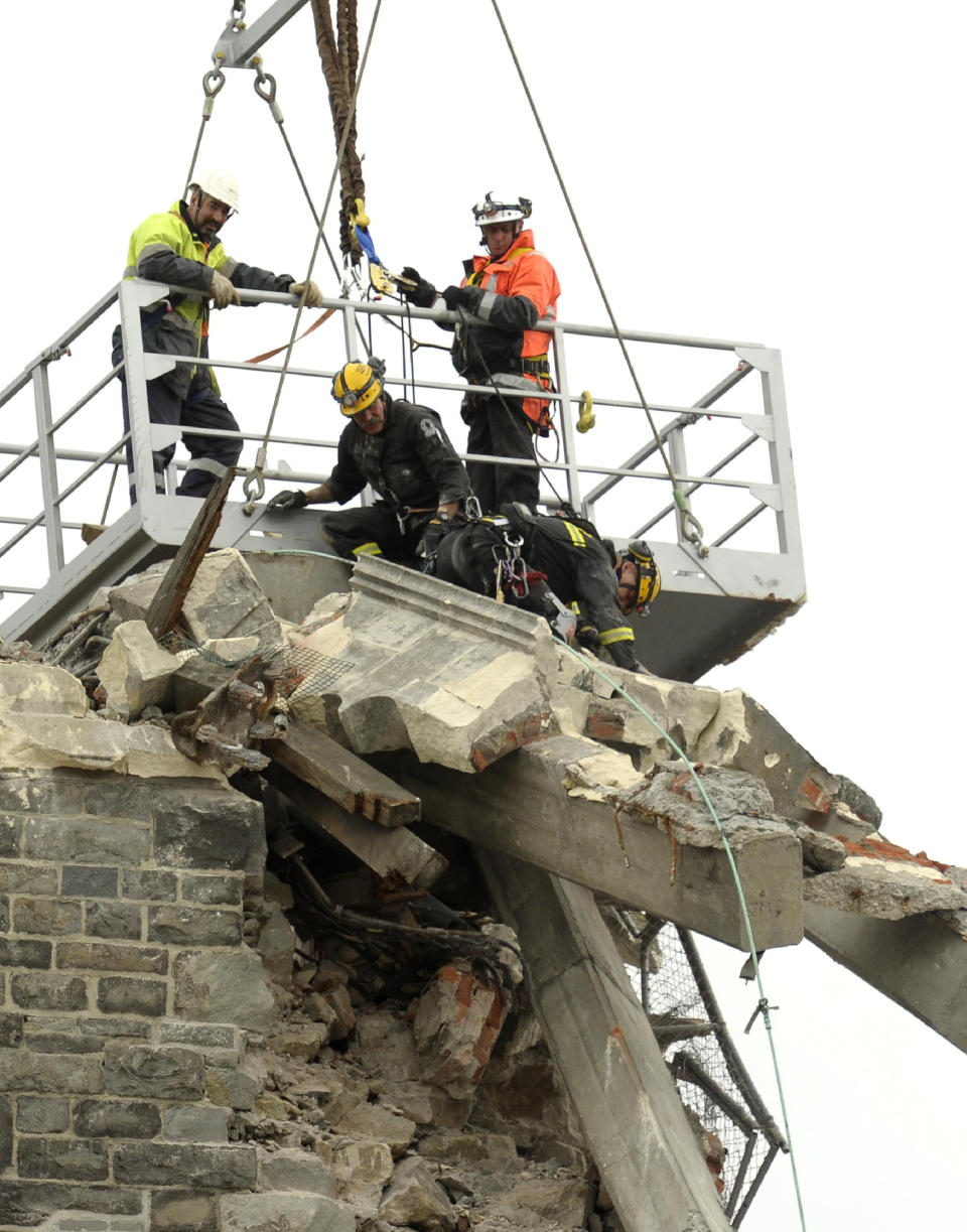 FILE - in this Feb. 25, 2011, file photo, recovery operation workers are lowered by crane onto the top of the earthquake damaged Christ Church Cathedral in Christchurch, New Zealand. The Christ Church Cathedral was arguably New Zealand's most iconic building before much of it crumbled during an earthquake 10 years ago. The years of debate that followed over whether the ruins should be rebuilt or demolished came to symbolize the paralysis that has sometimes afflicted the broader rebuild of Christchurch. But as the city on Monday, Feb. 22, 2021 marks one decade since the quake struck, killing 185 people and upending countless more lives, there are finally signs of progress on the cathedral. It's being rebuilt to look much like the original that was finished in 1904, only with modern-day improvements to make it warmer and safer. (AP Photo/Rob Griffith,File)