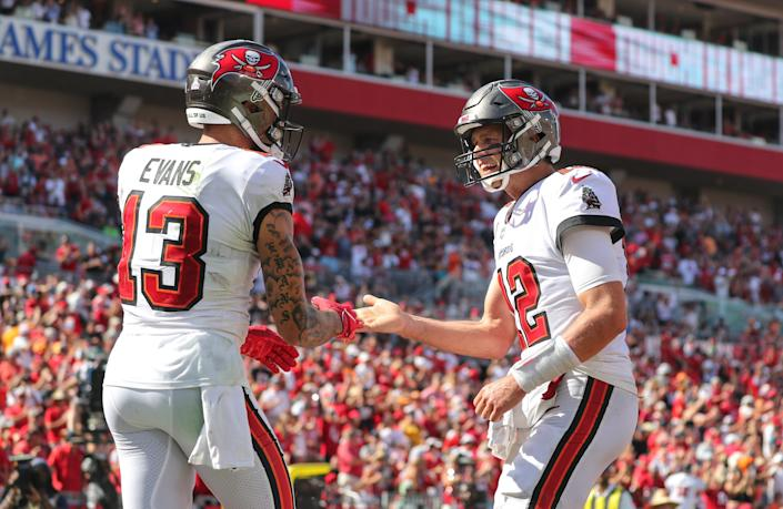 TAMPA, FL - OCTOBER 10: Tom Brady (12) of the Buccaneers congratulates Mike Evans (13) on scoring a touchdown during the regular season game between the Miami Dolphins and the Tampa Bay Buccaneers on October 10, 2021 at Raymond James Stadium in Tampa, Florida. (Photo by Cliff Welch/Icon Sportswire via Getty Images)