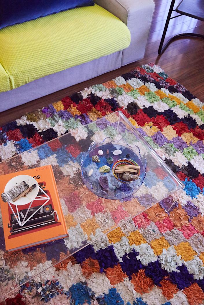 Here, Leah reinvented an IKEA sofa she already owned, converting the cushions with a fabric she found on Etsy. Then, she had blue velvet pillows custom made. The acrylic coffee table, also an item she's had for years, is livened up with the colorful rug beneath it.