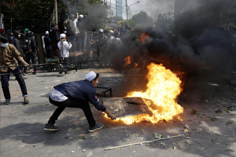 Protesters try to put out fire from a burning tyre in Jakarta, Indonesia, Wednesday, May 22, 2019. Supporters of an unsuccessful presidential candidate clashed with security forces in the Indonesian capital on Wednesday, burning vehicles and throwing rocks at police using tear gas and rubber bullets. (AP Photo/Dita Alangkara)