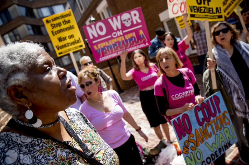 U.S. activist Medea Benjamin, co-founder of the anti-war group Code Pink, second from right, and others, sing together outside the Venezuelan Embassy in Washington, Thursday, May 2, 2019. Pro interim government opposition leader Juan Guaido supporters have blocked the entrances to the embassy, cutting off supplies to pro Nicolas Maduro supporters occupying the building. (AP Photo/Andrew Harnik)