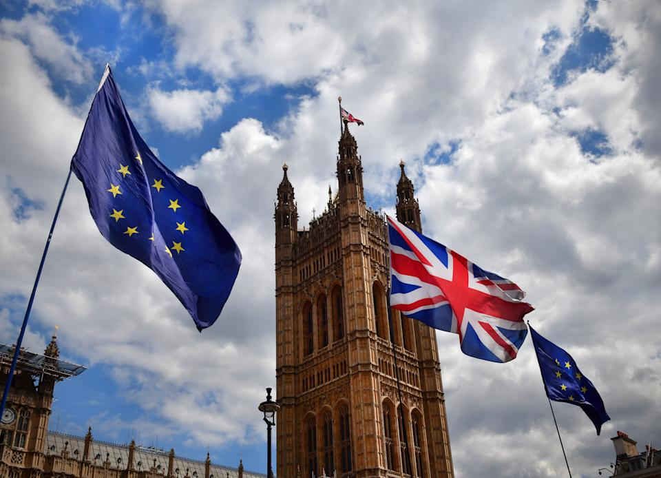 The European Union and UK flags flying outside tje House of Parliament in London as part of a Brexit protest