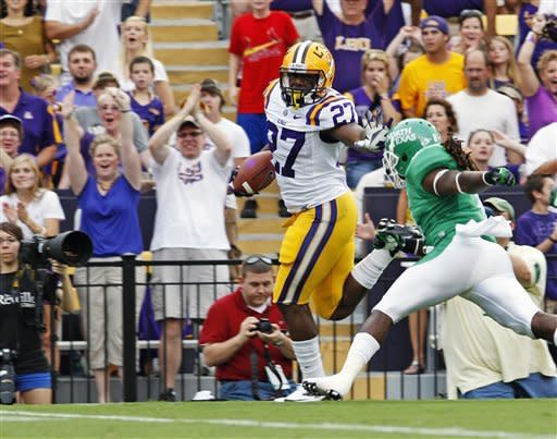 LSU running back Kenny Hilliard (27) stiff arms North Texas defensive back Marcus Trice (8) on his way to scoring a touchdown during the first half of an NCAA college football game in Baton Rouge, La., Saturday, Sept. 1, 2012. (AP Photo/Bill Haber)