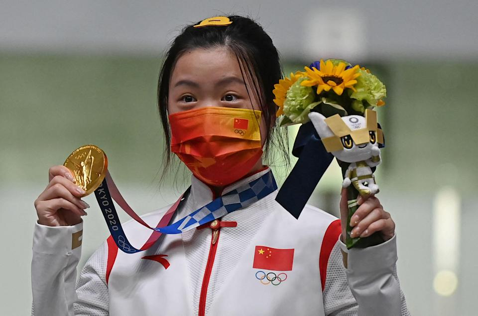 Gold medal winner China's Yang Qian celebrates on the podium after winning the women's 10m air rifle final during the Tokyo 2020 Olympic Games.
