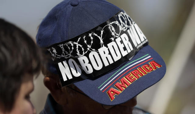 "Eli Cuello wears a ""no border wall"" bumper sticker on his cap during a sunrise procession and rally at La Lomita Chapel along the levee next to the Rio Grande in opposition to the wall the U.S. government wants to build, Saturday, Aug. 12, 2017, in Mission, Texas. The area would be the target of new barrier construction under the Trump administration's current plan. (AP Photo/Eric Gay)"