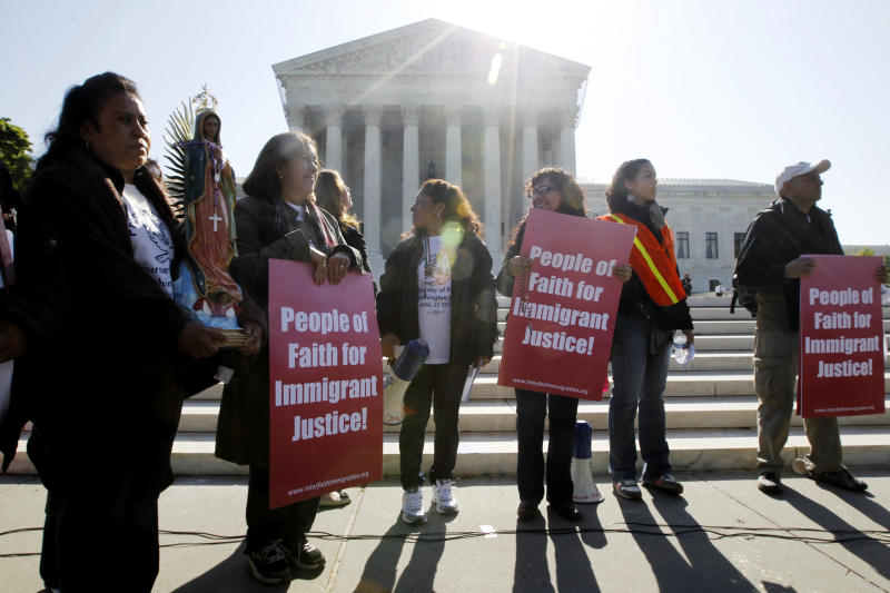 """Leonida Martinez, left, from Phoenix, Ariz., and others, take part in a demonstration in front of the Supreme Court in Washington, Wednesday, April 25, 2012, as the court questions Arizona's """"show me your papers"""" immigration law . (AP Photo/Charles Dharapak)"""