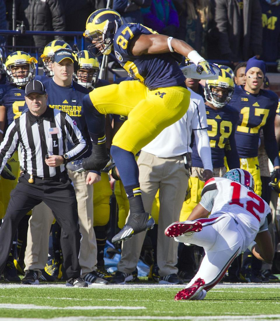 Michigan tight end Devin Funchess (87) leaps over Ohio State cornerback Doran Grant (12) in the second quarter of an NCAA college football game in Ann Arbor, Mich., Saturday, Nov. 30, 2013. (AP Photo/Tony Ding)