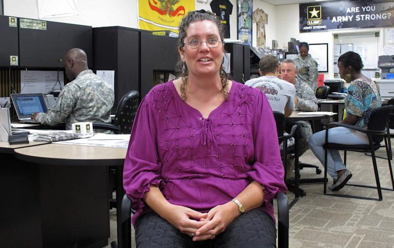 In this Oct. 17, 2012 photo, Leslie Ann Sully discusses her years in the active-duty Army, stationed in West Germany, during an interview  in Columbia, S.C. Sully is a civilian who works with the U.S. Army Recruiting Battalion in South Carolina but volunteered to leave the active duty ranks during cutbacks in the 1990s. (AP Photo/Jeffrey Collins)