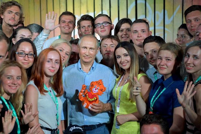 Russian President Vladimir Putin posing with a group of youngsters at an education forum in Crimea last year. The 'Elections: Adults Only' campaign hopes to bring more young voters to the polling booths (AFP Photo/Alexei Druzhinin)