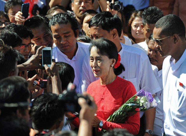 Aung San Suu Kyi speaks to supporters as she leaves the D. Wave Journal office in Yangon on December 30, 2012