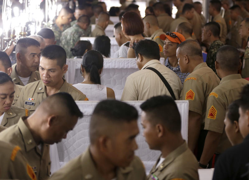 Philippine Marines pay tribute to the flag-draped coffins of seven fellow marines who were killed Saturday in a clash with Abu Sayyaf militants in Jolo, southern Philippines, during the wake at the Philippine Marines headquarters at Fort Bonifacio in Taguig city, east of Manila, Philippines Monday, May 27, 2013. At least seven Filipino marines and an equal number of Abu Sayyaf militants were killed in a clash in a new U.S.-backed offensive aimed at rescuing six foreign and Filipino hostages and stopping the al-Qaida-linked gunmen from staging more kidnappings in the country's south, a military commander said Sunday. (AP Photo/Bullit Marquez)