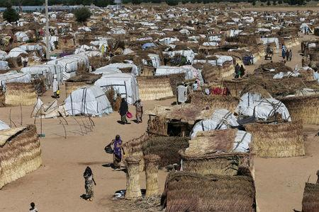 FILE PHOTO: People walk inside the Muna Internally displace people camp in Maiduguri, Nigeria