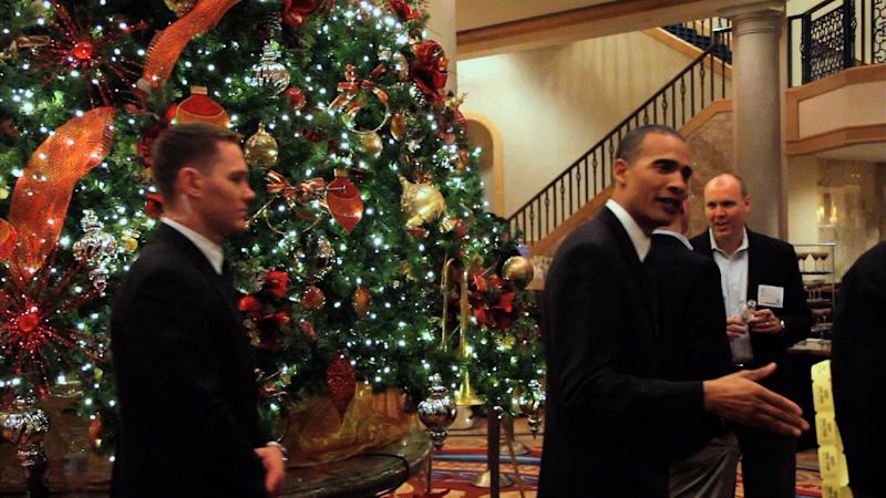 """In this image from video, President Barack Obama lookalike Larry Graves greets people during an appearance. Graves has the security detail, the prominent ears and the U.S. flag pin, but substitute teacher Graves is no Barack Obama. He's a professional lookalike for the president. They have something else in common, too: a frantic schedule leading up to the inauguration. """"It's definitely a busy time,"""" Graves said. """"Between the campaign season and the inauguration, it's been prime time. Barack Obama is a respectable guy. People want to have him at their parties."""" (AP Photo)"""