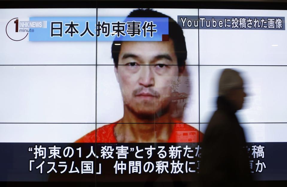 """A man walks past screens displaying a television news programme showing an image of Kenji Goto, one of two Japanese citizens taken captive by Islamic State militants, on a street in Tokyo January 25, 2015. Japanese Prime Minister Shinzo Abe on Sunday called the apparent killing of Japanese captive Haruna Yukawa by Islamic State militants """"outrageous and impermissible,"""" and again called for the group to release Goto, the second Japanese national they are holding. The words on the screen read """"Japanese hostage incident"""" (top L) and """"a still image posted on YouTube"""" (top R). REUTERS/Yuya Shino (JAPAN - Tags: POLITICS CIVIL UNREST MEDIA HEADSHOT TPX IMAGES OF THE DAY CRIME LAW)"""