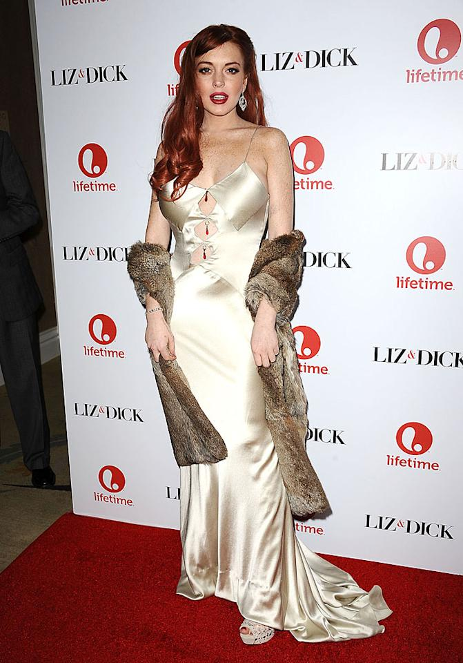 "Lindsay Lohan was probably going for old Hollywood glamour at the Los Angeles premiere of ""Liz & Dick"" on Tuesday night, but it was a look that would have made Elizabeth Taylor roll over in her grave. The actress hit the red carpet in a cheap, negligee-like gown which allowed her to show off a little too much skin. To top things off, Lindsay accessorized with what appeared to be roadkill. Here's to hoping her stole was at least made of fake fur! (11/20/2012)"