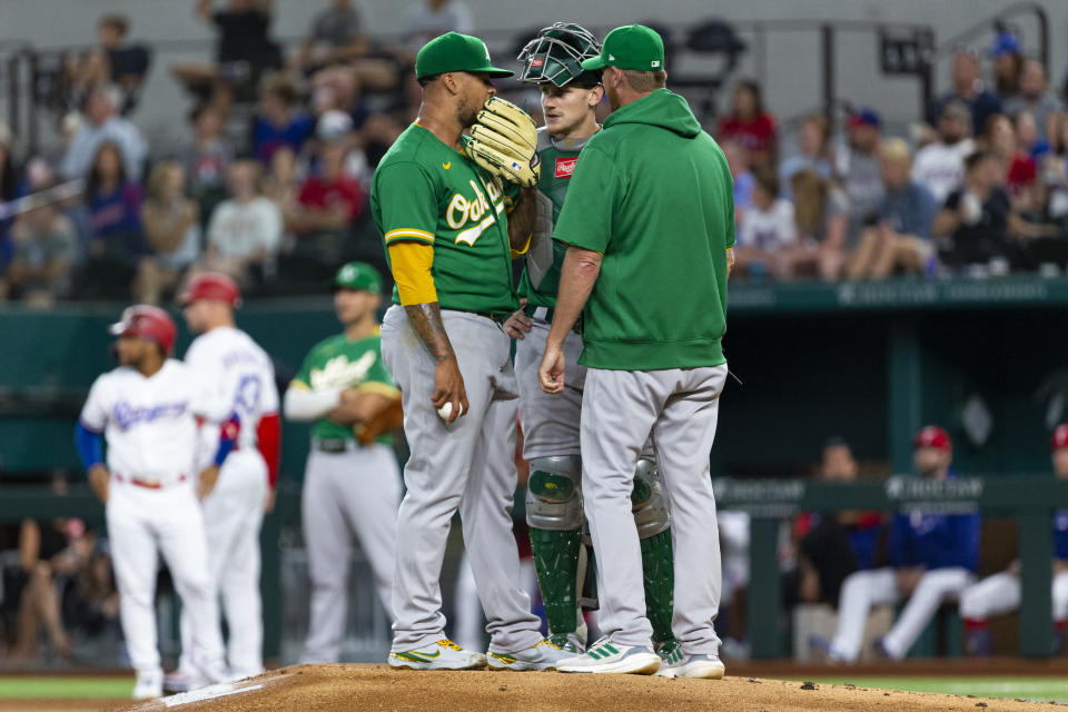 Oakland Athletics starting pitcher Frankie Montas, foreground left, catcher Sean Murphy, foreground center, and pitching coach Scott Emerson, right, talk on the mound during the first inning of a baseball game against the Texas Rangers, Monday, June 21, 2021, in Arlington, Texas. (AP Photo/Sam Hodde)