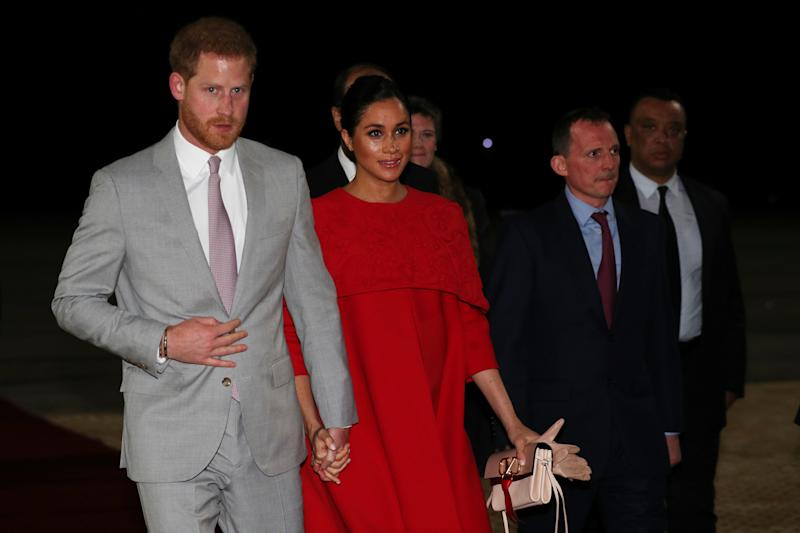 32204aafec9 Pregnant Meghan Markle looks elegant in a red Valentino dress as she  arrives in Morocco