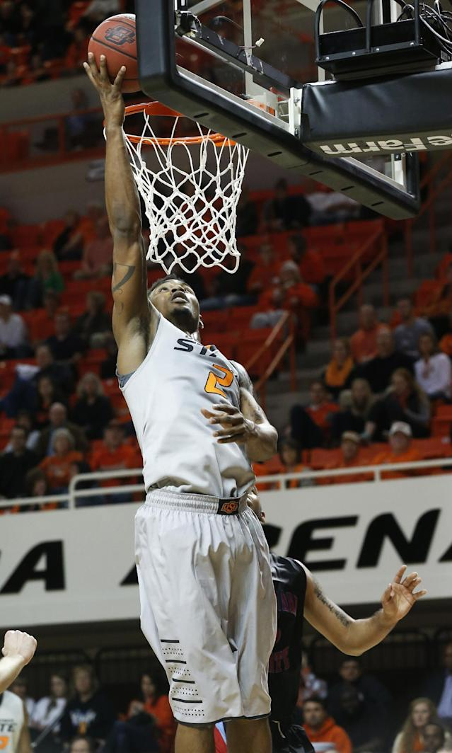 Oklahoma State wing Le'Bryan Nash (2) shoots in front of Delaware State forward Tyshawn Bell (5) in the second half of an NCAA college basketball game in Stillwater, Okla., Tuesday, Dec. 17, 2013. Oklahoma State won 75-43. (AP Photo/Sue Ogrocki)