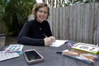 Kara McKlemurry poses for a photo while writing Thanksgiving notes to family and friends at her home Thursday, Nov. 19, 2020, in Clearwater, Fla. On any normal Thanksgiving Day, McKlemurry and her husband would drive from their home to one of two places: his family's home in another part of Florida or her family's house in Alabama. This year, McKlemurry informed her family there would be no visits because of the pandemic. (AP Photo/Chris O'Meara)