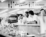 <p>Two men share a drink at the soda bar inside a supermarket. </p>