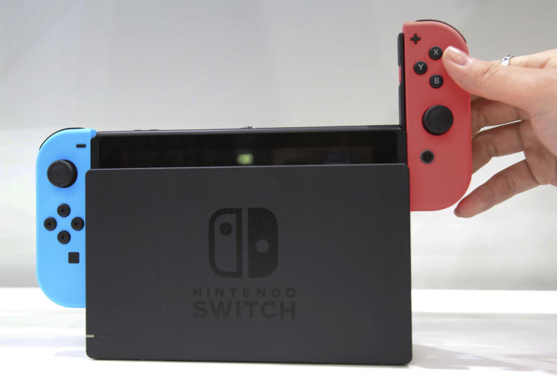 A model puts the controller on to the Nintendo Switch during a presentation event of the new Nintendo Switch in Tokyo, Friday, Jan. 13, 2017. Nintendo Co. said Friday that its Nintendo Switch video game console will sell for 29,980 yen (about $260) in Japan, starting March 3. (AP Photo/Koji Sasahara)