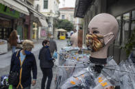 Women walk past a dummy wearing a face mask, in central Athens, Thursday, Oct. 29, 2020. Greece is seeing a record-breaking jump in the number of confirmed COVID-19cases for the second consecutive day, with 1,547 new cases announced Wednesday, Oct 28, and 10 new deaths. (AP Photo/Petros Giannakouris)