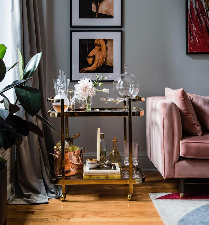 "<div class=""caption""> The brass bar cart, which was on Natasha's must list for her new place, adds to the glamorous palette. </div>"