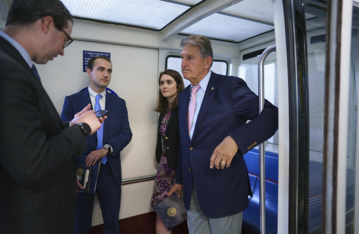 Sen. Joe Manchin, D-W.Va., a key infrastructure negotiator, talks to his staff on the Senate subway after working behind closed doors with other Democrats in a basement room at the Capitol in Washington, Wednesday, June 16, 2021. (AP Photo/J. Scott Applewhite)