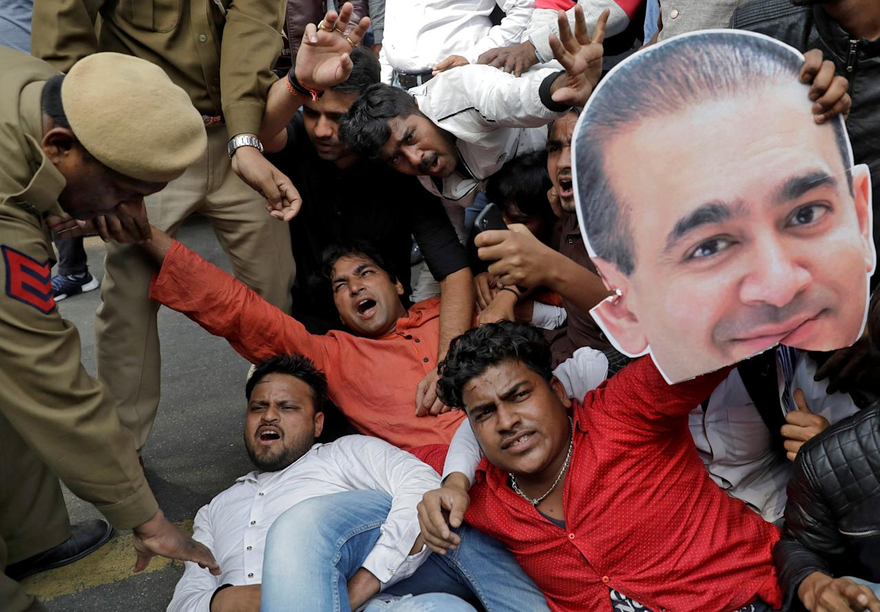An activist of the youth wing of India's main opposition Congress party holds a cut-out with an image of billionaire jeweller Nirav Modi during a protest in New Delhi, India February 16, 2018. REUTERS/Saumya Khandelwal     TPX IMAGES OF THE DAY