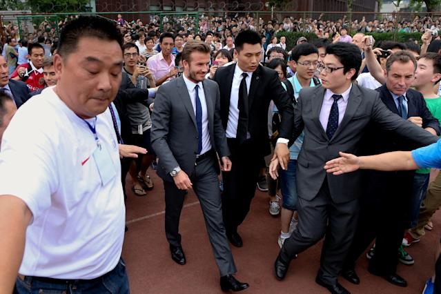 David Beckham walks to meet his fans before a stampede caused by fans storming a security cordon in a university in Shanghai Thursday June 20, 2013. Fans eager to see the soccer superstar stormed a police cordon in a stampede that injured seven people including five security personnel. (AP Photo) CHINA OUT