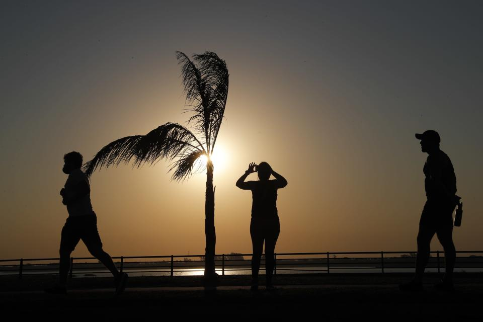 People are silhouetted against the sky with a setting sun in Asuncion, Paraguay, Saturday, Aug. 1, 2020, amid the new coronavirus pandemic. (AP Photo/Jorge Saenz)