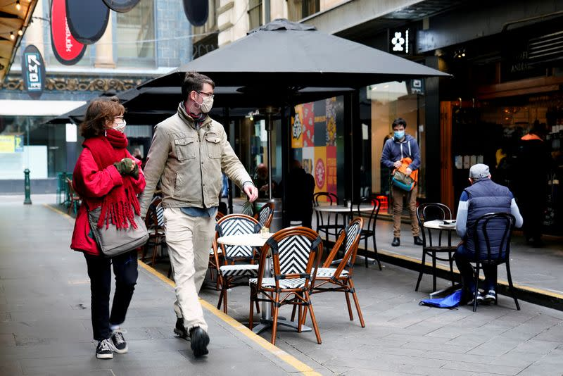 FILE PHOTO: People walk past a cafe after the coronavirus disease (COVID-19) restrictions were eased for the state of Victoria, in Melbourne