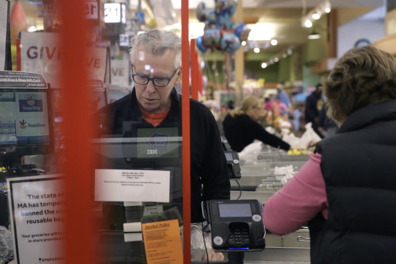 Cashier George Wallace, of Quincy, Mass., center, works while standing behind a plastic shield Thursday, March 26, 2020, at the checkout in a grocery store, in Quincy, Mass. Grocery stores across the U.S. are installing protective plastic shields at checkouts to help keep cashiers and shoppers from infecting each other with the coronavirus. The new coronavirus causes mild or moderate symptoms for most people, but for some, especially older adults and people with existing health problems, it can cause more severe illness or death. (AP Photo/Steven Senne)