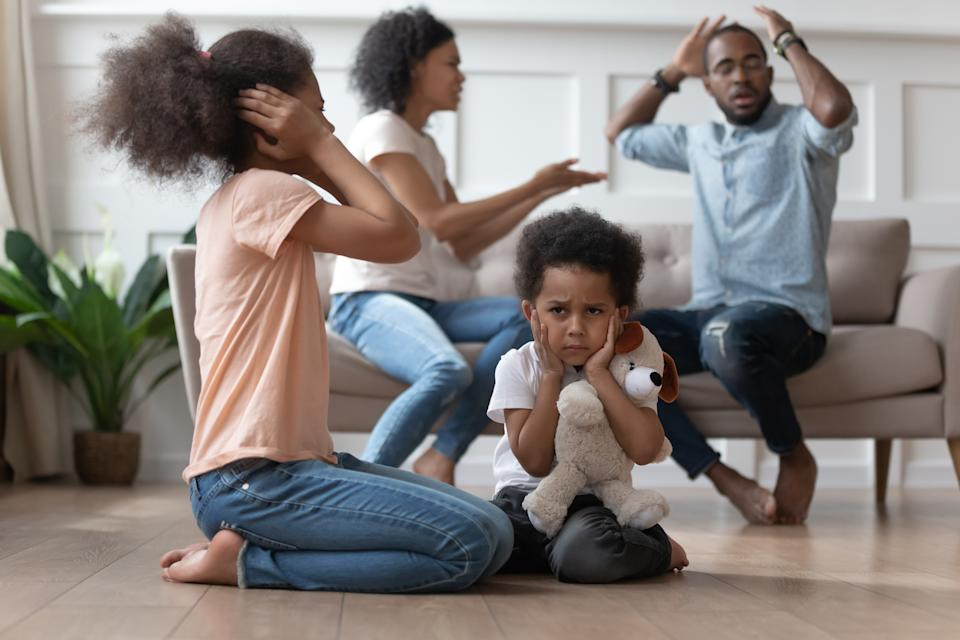 Upset african kids closing ears hurt by parents fighting arguing at home, sad stressed little innocent children suffer from family problems conflicts, unhappy mom dad shouting quarreling divorcing