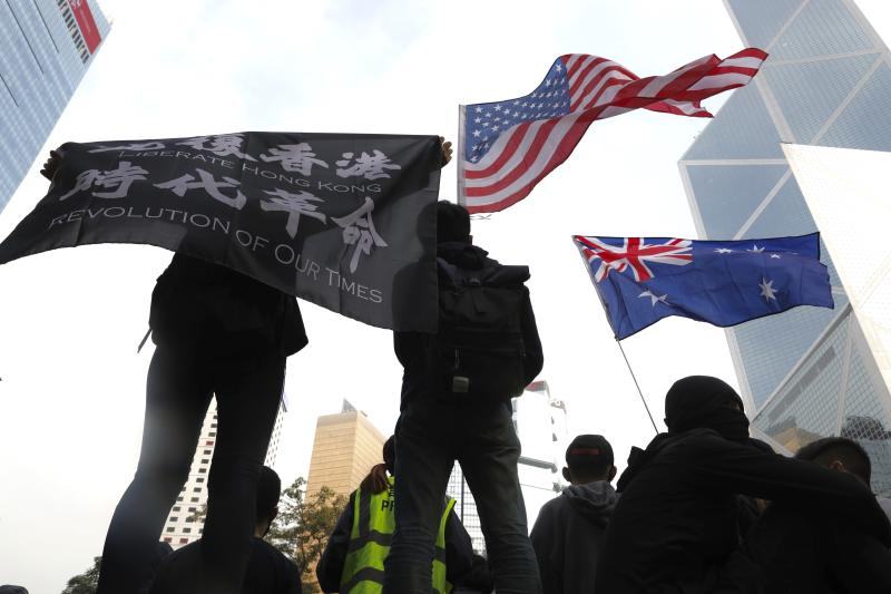 Participants wave a U.S. flag and a colonial flag during a rally demanding electoral democracy and call for boycott of the Chinese Communist Party and all businesses seen to support it in Hong Kong, Sunday, Jan. 19, 2020. Hong Kong has been wracked by often violent anti-government protests since June, although they have diminished considerably in scale following a landslide win by opposition candidates in races for district councilors late last year. (AP Photo/Ng Han Guan)