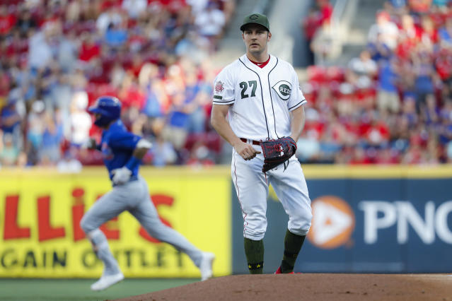 Cincinnati Reds starting pitcher Trevor Bauer (27) reacts after giving up a solo home run to Chicago Cubs' Nicholas Castellanos, left, in the first inning of a baseball game, Friday, Aug. 9, 2019, in Cincinnati. (AP Photo/John Minchillo)