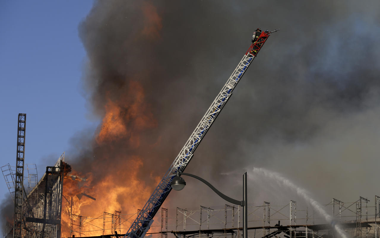 A firefighter prepares to spray water on a fire in San Francisco, Tuesday, March 11, 2014. The major fire burning in San Francisco's Mission Bay neighborhood sent an enormous plume of black smoke high into the sky. There were no initial reports of injuries. The four-alarm fire that began about 5 p.m. was ravaging a high-rise building under construction and moving down a block. Fire-suppression systems had not yet been installed in the building, making the battle against the blaze more difficult, Fire Department spokeswoman Mindy Talmadge said. (AP Photo/Jeff Chiu)