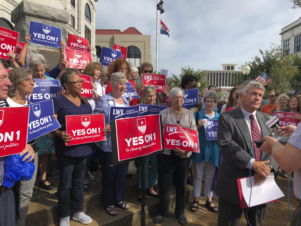 "FILE - In this Aug. 31, 2018 file photo, supporters of Missouri's redistricting ballot measure hold signs behind former state Sen. Bob Johnson as he serves as their spokesman during a press conference outside the Cole County Courthouse in Jefferson City, Mo .Two years after Missouri voters enacted a first-of-its-kind initiative intended to create ""partisan fairness"" in voting districts, they have changed their minds. (AP Photo/David A. Lieb, File)"