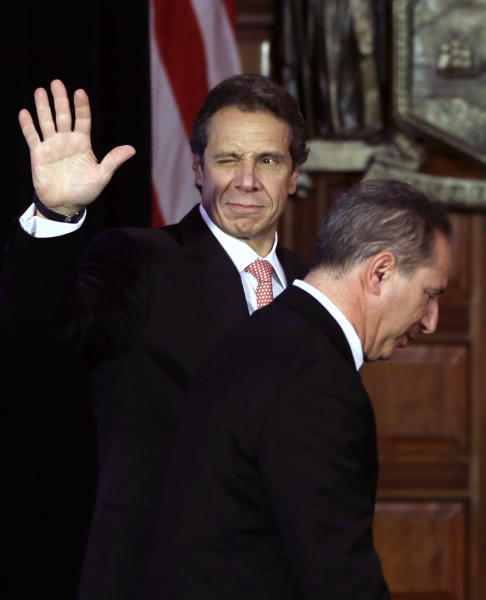 New York Gov. Andrew Cuomo, left, winks and waves as he and Howard Glaser, New York state director of operations, leave the Red Room after a cabinet meeting at the Capitol on Thursday, Sept. 27, 2012, in Albany, N.Y. Cuomo is calling a summit to boost the beer and wine industries in New York just months after a similar effort began to try to make New York the nations largest producer of Greek-style yogurt. (AP Photo/Mike Groll)