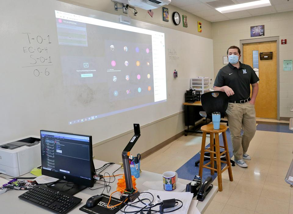 Clancy Bryant, an English teacher in Tuscaloosa, Alabama, teaches both in-person students and remote students who see him through the camera.
