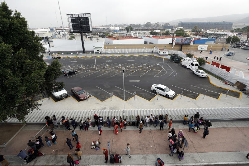 Migrants line up along an entrance to the border crossing as they wait to apply for asylum in the United States, Tuesday, July 16, 2019, in Tijuana, Mexico. Dozens of immigrants lined up Tuesday at a major Mexico border crossing, waiting to learn how the Trump administration's plans to end most asylum protections would affect their hopes of taking refuge in the United States. (AP Photo/Gregory Bull)