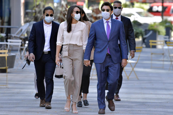 Former Fall River, Mass. Mayor Jasiel Correia, right, arrives with his wife and his wife Jenny Fernandes, center, and family members for a court appearance at the John Joseph Moakley United States Courthouse, Monday, Sept. 20, 2021, in Boston. Correia, who was elected at the age of 23 with promises to rejuvenate the struggling mill city, was scheduled to be sentenced for stealing from investors in a smartphone app he created and extorting hundreds of thousands of dollars in bribes from marijuana businesses. (AP Photo/Josh Reynolds)
