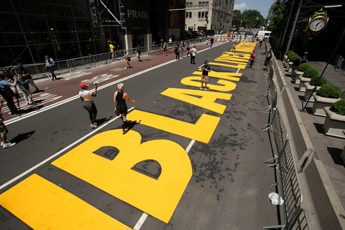 Volunteers walk along a Black Lives Matter mural that was painted on Fifth Avenue in front of Trump Tower, Thursday, July 9, 2020, in New York.